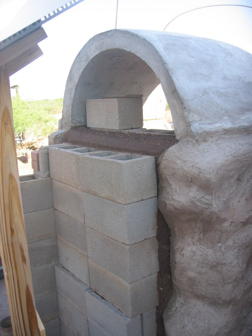 Paper adobe mix is packed between loose concrete blocks, which serve as the form. Rebar was already put in place when the earthbag structural walls were built.
